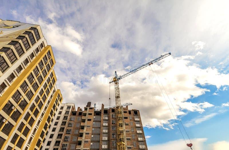 起重机和高层建筑物建设中反对蓝天 免版税库存照片