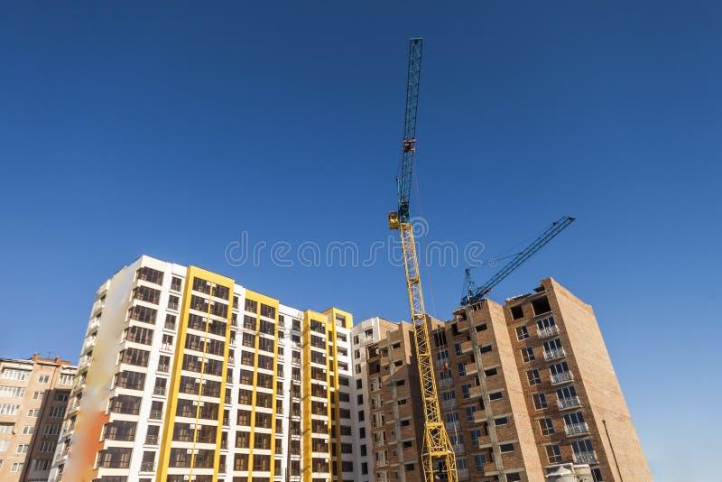 起重机和高层建筑物建设中反对蓝天 免版税图库摄影