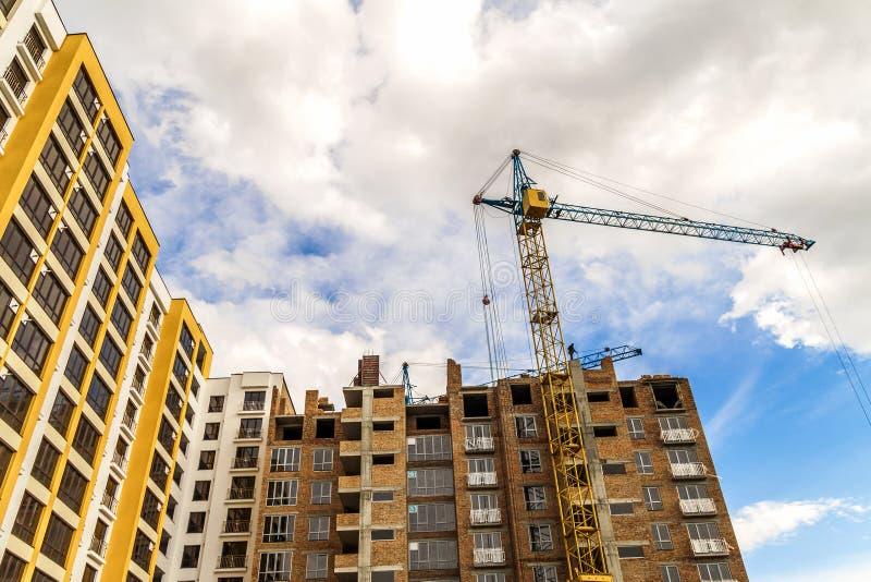 起重机和高层建筑物建设中反对蓝天 图库摄影