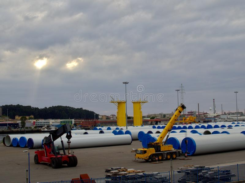 起重机在阿维莱斯港口装载向着海岸的近海处风塔的部分 免版税图库摄影