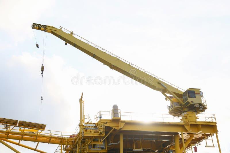 起重机操作在平台的调动货物和从供应小船的移动的货物,抬举费力在油和煤气建筑平台 库存图片