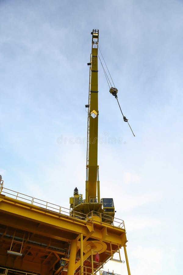 起重机操作在平台的调动货物和从供应小船的移动的货物,抬举费力在油和煤气建筑平台 免版税库存照片