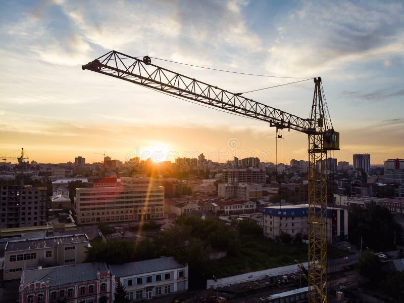 起重机,在建筑工地剪影的建筑用起重机与剧烈的天空在平衡的背景中,技术运输 免版税库存照片