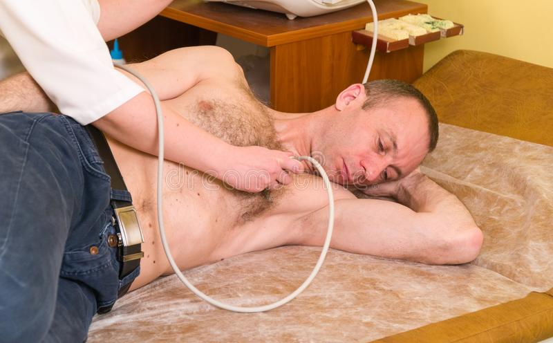 超声波 心脏病学 心脏的考试与超声波的 有超合理的医生心脏科医师回顾的患者 图库摄影