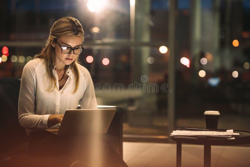 超时工作在办公室的女实业家 免版税图库摄影