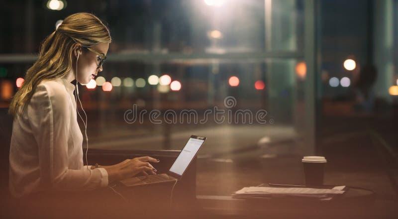 超时工作在办公室的女实业家 免版税库存照片