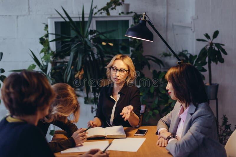 超时工作概念 后工作在晚上的小组女性企业队 免版税库存照片