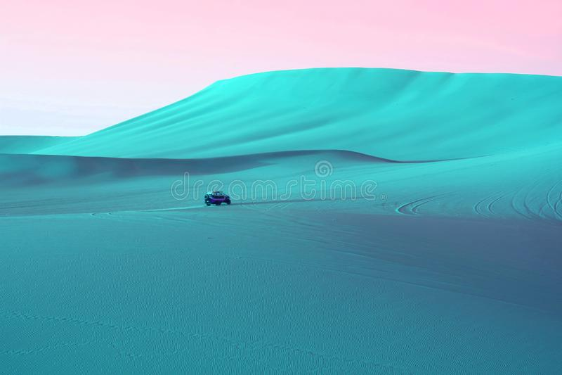 超现实的流行艺术称呼了土耳其玉色色的沙丘和连续沙地汽车在粉红天空下 免版税库存照片