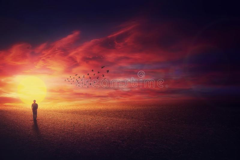 超现实的风景视图作为走在美好的日落背景前面的流浪汉人剪影和飞行的鸟群  免版税库存照片