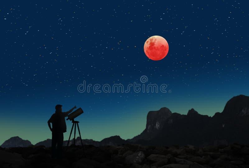 超级名门出身月亮蚀和一个人有望远镜的 库存图片