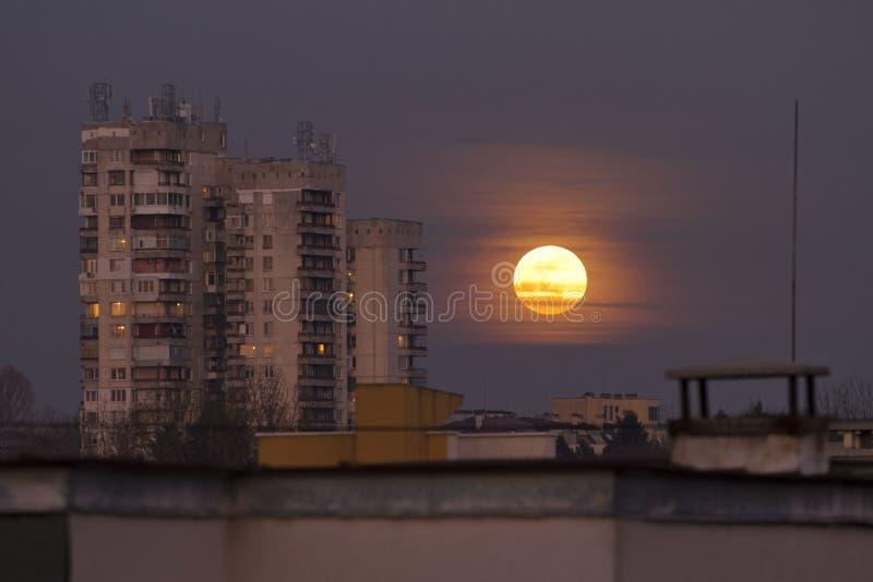 超级名门出身月亮2018年1月31日从Easterm欧洲,保加利亚,索非亚 在海运的蚀月球月亮 在大厦旁边的超级月亮 库存图片
