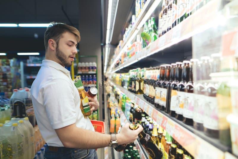 超级市场买家采取啤酒在架子外面 人得到了啤酒的充分的手,当购物时 免版税库存图片