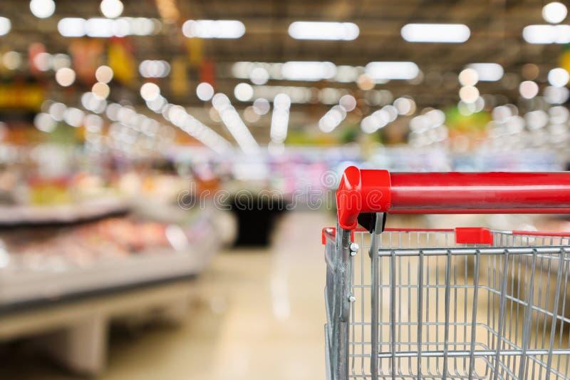 超级市场杂货店有与空的手推车的水果和蔬菜架子内部defocused背景 库存图片