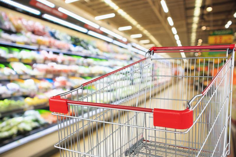 超级市场杂货店有与空的手推车的水果和蔬菜架子内部defocused背景 库存照片