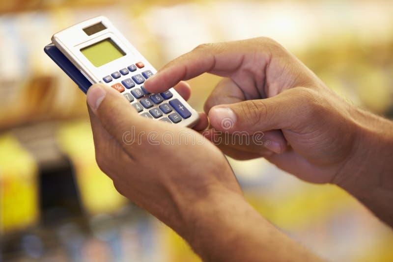 超级市场杂货走道的人使用计算器的 库存图片