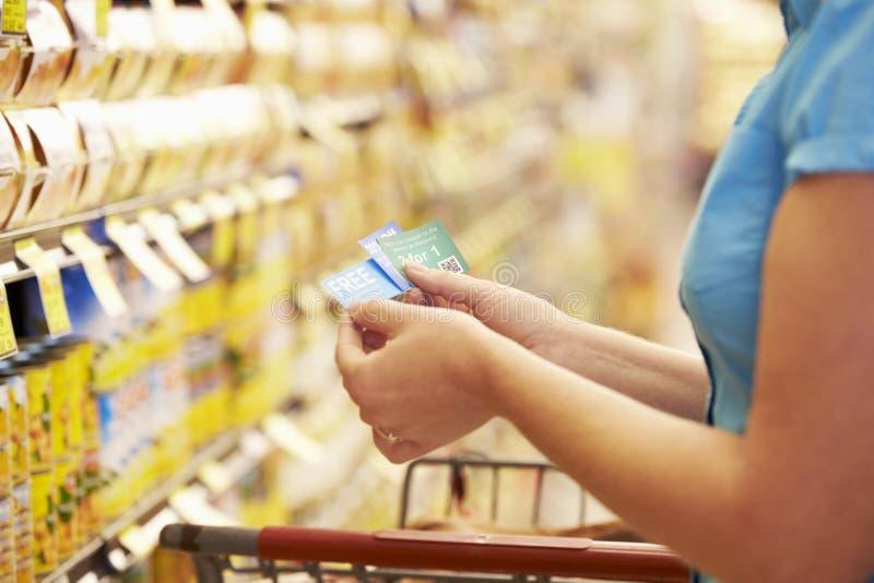 超级市场杂货走道的妇女有优惠券的 库存照片