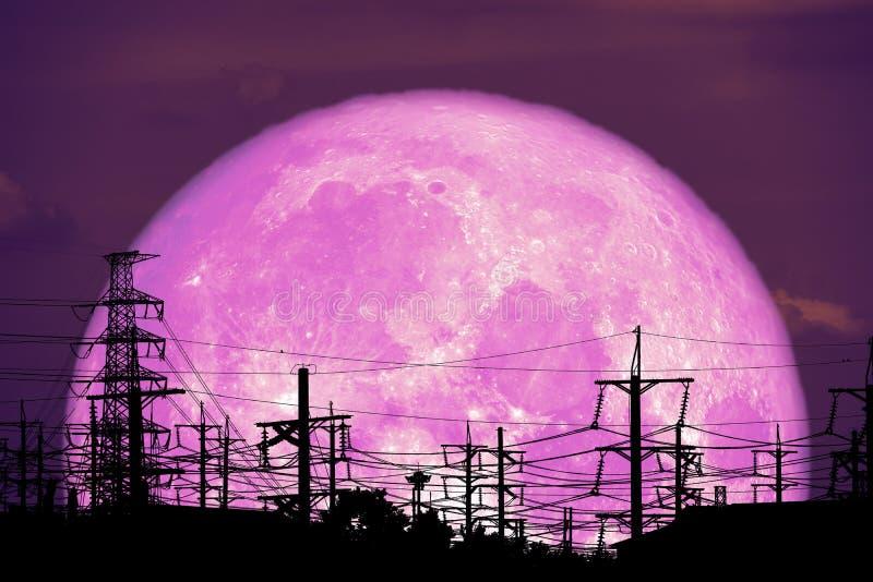 超级牛奶月亮在夜空的剪影电杆 免版税库存照片