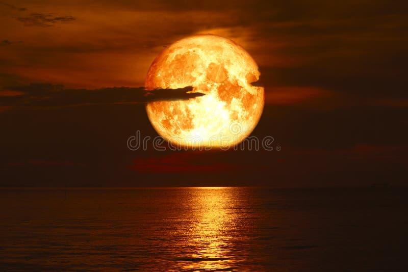 超级玫瑰色在海的血液月亮后面剪影云彩红色天空 库存照片