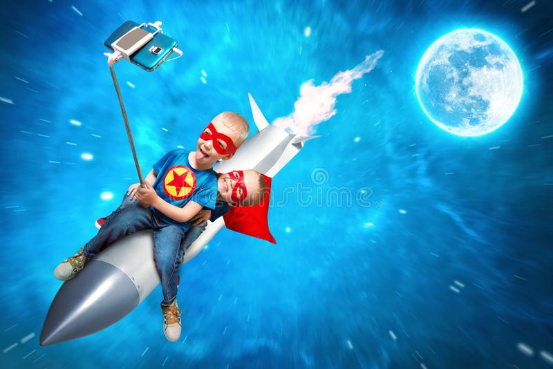 超级英雄服装的孩子在火箭的空间飞行并且射击在一个手机的一selfie 库存照片