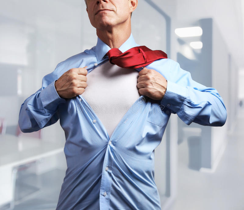 超级英雄 撕下他的衬衣的成熟商人  库存照片