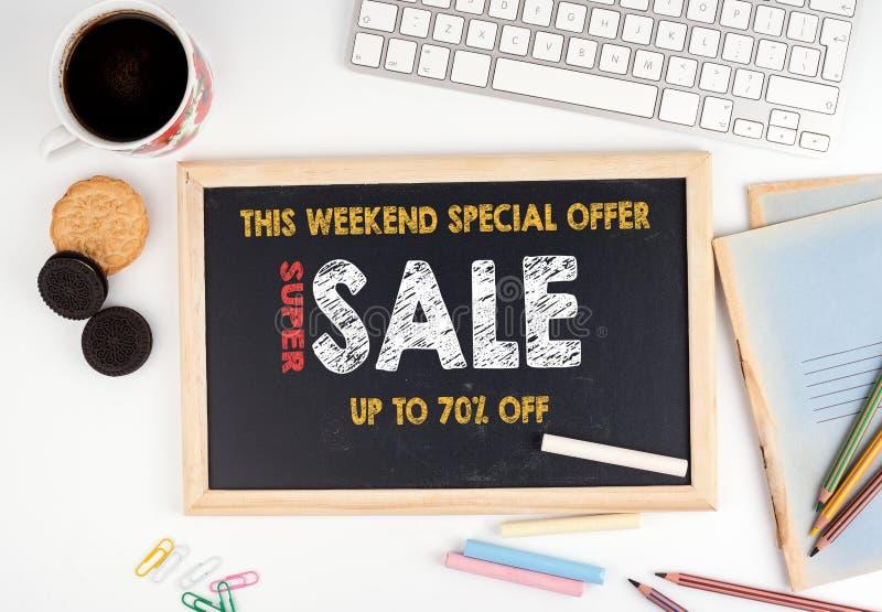 超级销售,这个周末特价优待 在白色办公桌上的黑板 免版税库存图片