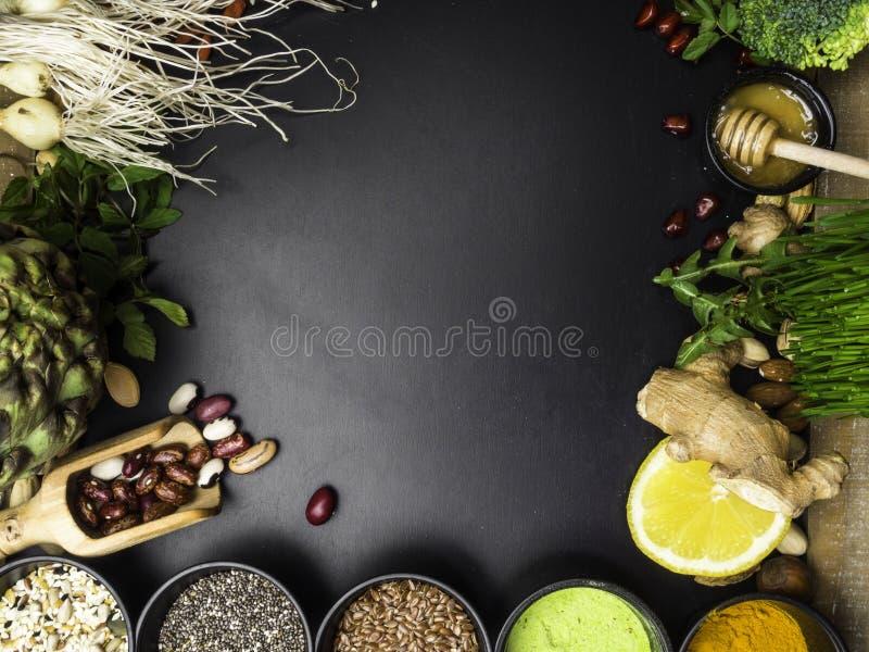 超级食物或素食食物概念 种子,豆,菜,麦子幼木,蜂蜜,健康烹调的柑橘在黑色 库存照片