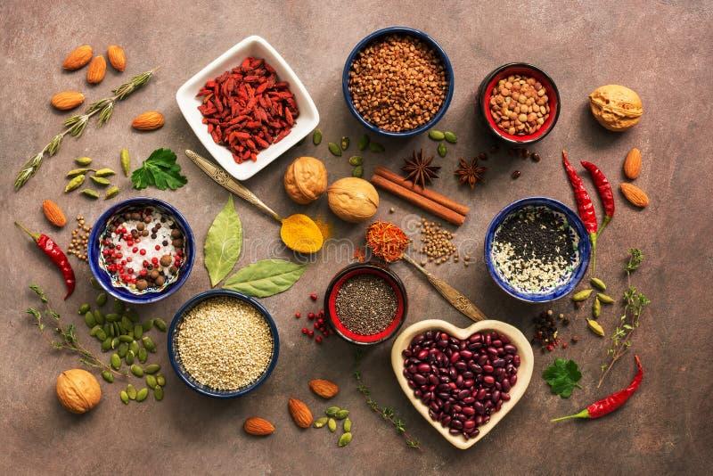 超级食物背景,各种各样的谷物,豆类,香料,草本,坚果 烹调的各种各样的调味料在棕色背景 ?? 库存图片
