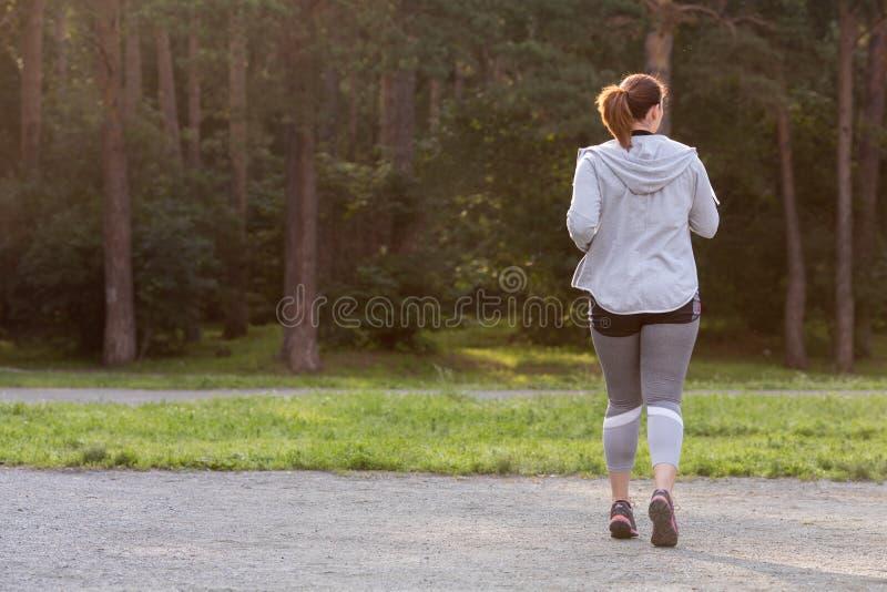 超重妇女后面赛跑 在重量白人妇女的美好的腹部概念损失 免版税图库摄影