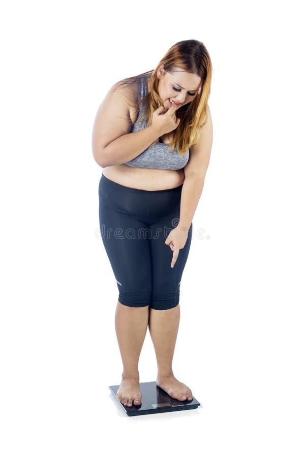 超重妇女惊吓与秤 免版税库存图片