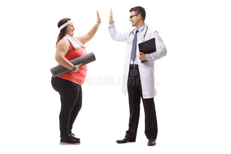 超重妇女高fiving与医生 免版税库存图片