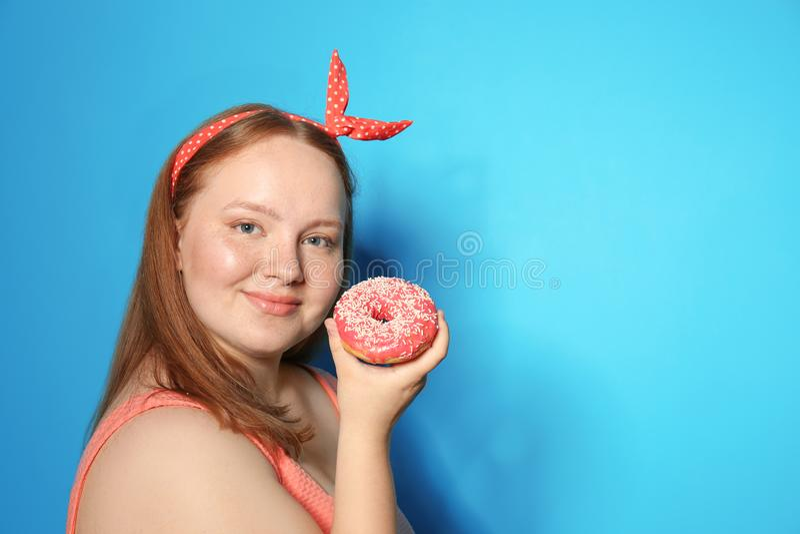 超重少妇用在颜色背景的多福饼 免版税图库摄影