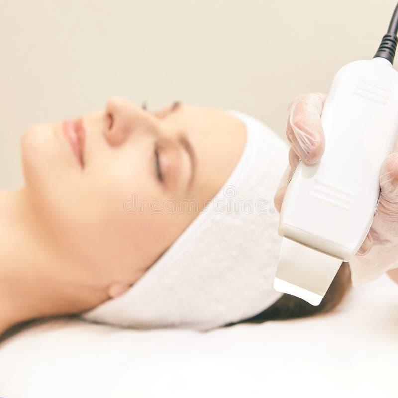 超音波皮肤设备 妇女面孔整容术治疗 女孩诊所面部做法 反粉刺手术清洁 免版税库存图片