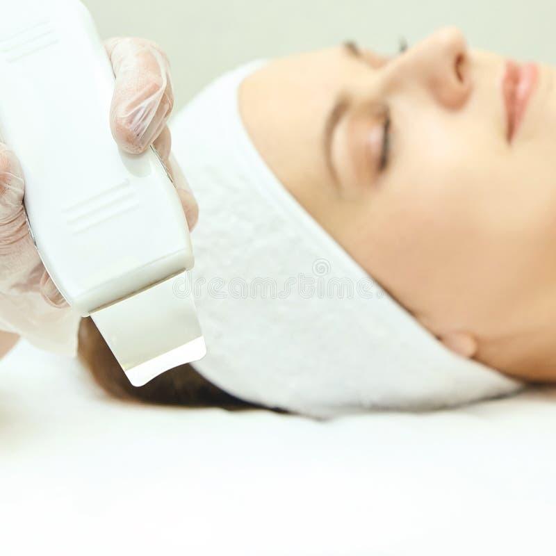 超音波皮肤设备 妇女面孔整容术治疗 女孩诊所面部做法 反粉刺手术清洁 免版税库存照片