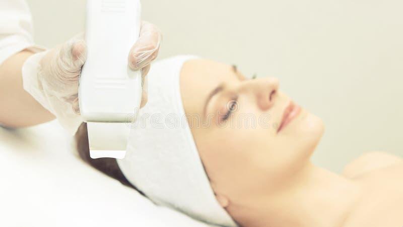 超音波皮肤设备 妇女面孔整容术治疗 女孩诊所面部做法 反粉刺手术清洁 图库摄影