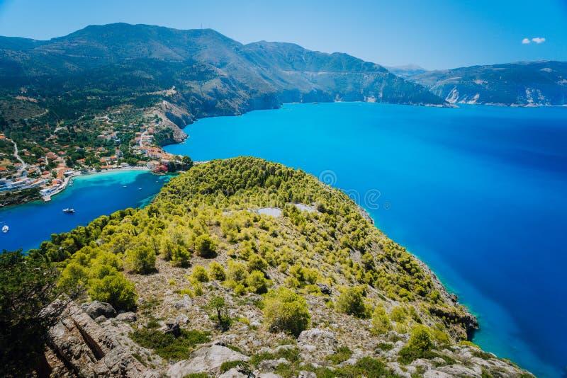 超Assos村庄宽射击早晨光的, Kefalonia 希腊 美丽的绿松石色的海湾盐水湖水 免版税库存照片
