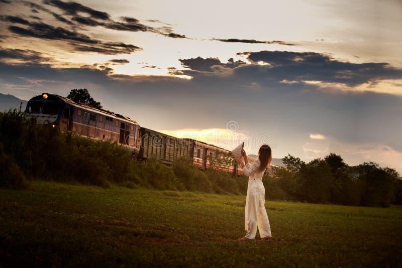 越南后侧方视图的白肤金发的女孩反对火车 免版税库存图片
