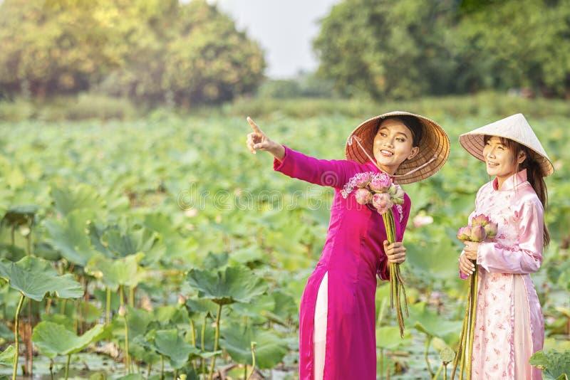 越南女孩邀请朋友看莲花 有桃红色莲花的越南礼服 女性划船 图库摄影