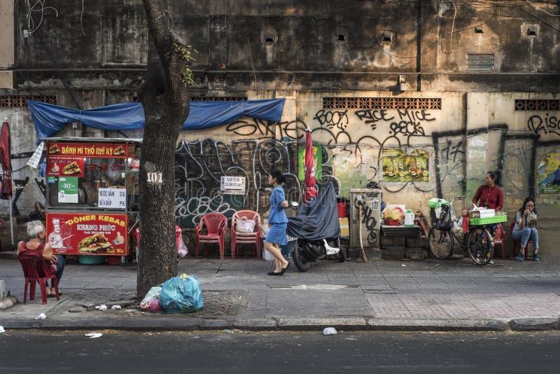 越南居民由老墙壁享受在街道上的一个寂静片刻在胡志明市,越南 库存照片