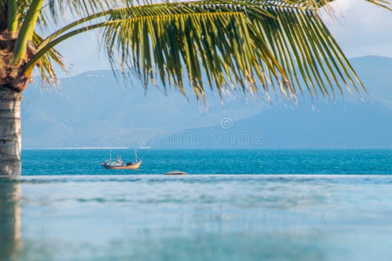 越南渔船航行过去在棕榈树下 免版税库存照片