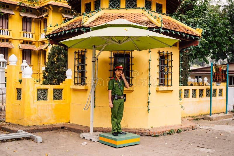越南警察站立联合国der伞和投入某事在他的眼睛外面,当是当班在河内,越南时 库存照片