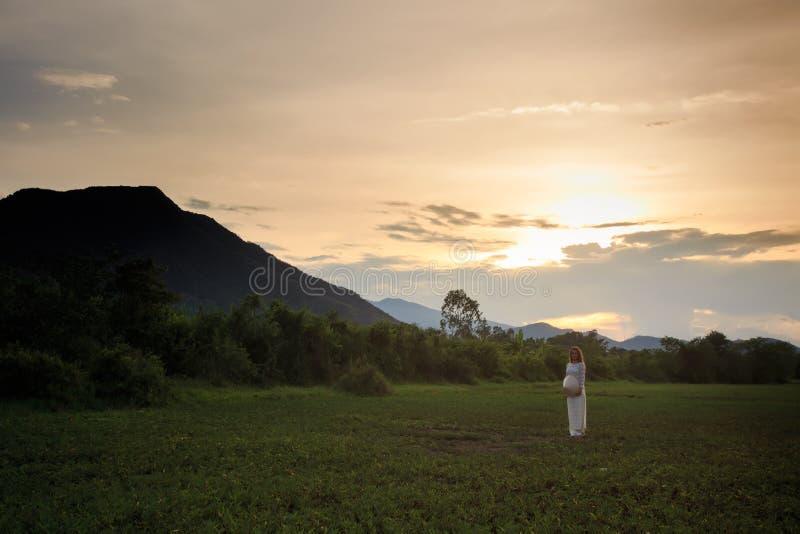 越南语的白肤金发的女孩穿戴在领域的后侧方视图 免版税图库摄影