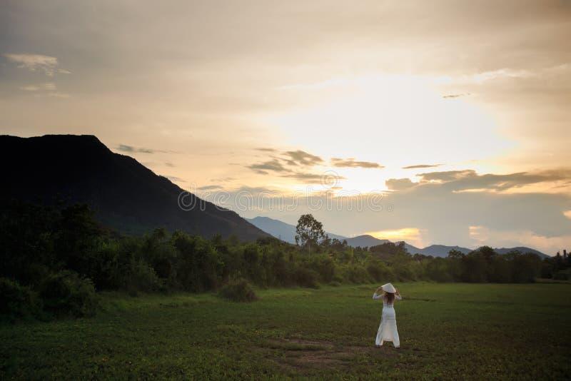 越南语的白肤金发的女孩穿戴在领域的后侧方视图 免版税库存图片