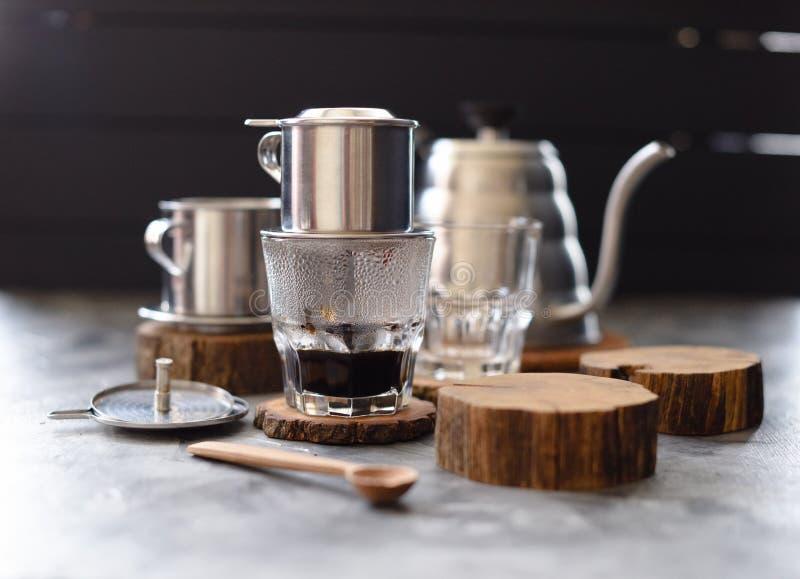 越南黑滴水咖啡 传统越南咖啡壶phin和鹅脖子水壶在木平板在黑暗的背景 免版税库存图片