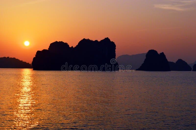越南-下龙湾-石灰石在日落更加接近的石灰岩地区常见的地形剪影 库存图片