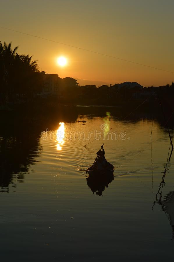 越南- Hoi风景在剪影的小划船渔船在日落的星期四好的妙语河 库存图片