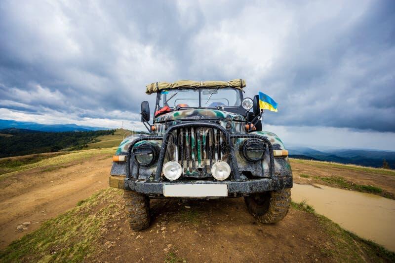 越野驾驶的吉普是在山的小山顶部 免版税库存照片
