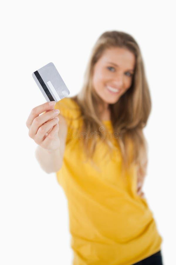 趋向于信用卡的一位白肤金发的学员的纵向 库存图片