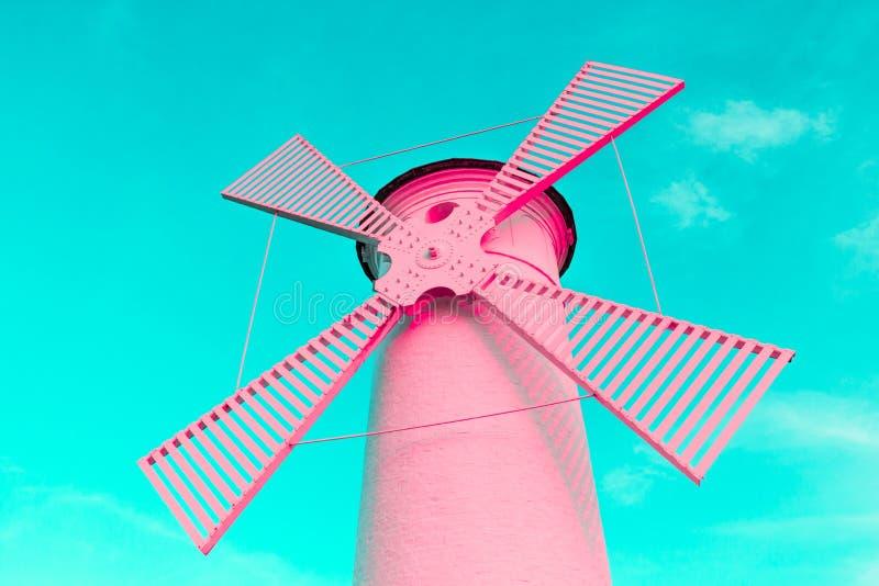 趋向在蓝色淡色背景的颜色珊瑚桃红色超现实的灯塔风车 免版税库存图片