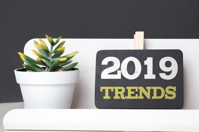 趋向2019年在有现代笔盒和绿色植物的黑板在桌和深灰墙壁上的白色罐的在办公桌 远期 免版税库存图片