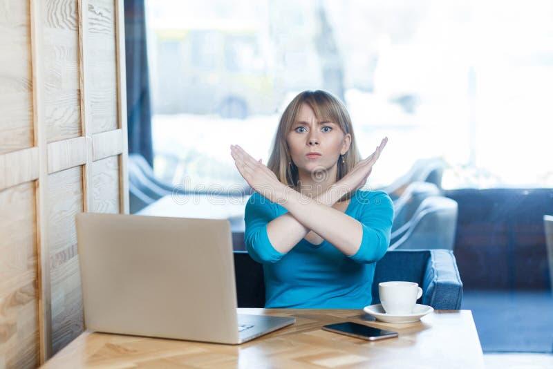 足够!警告有金发的积极的少女画象在T恤杉女衬衫在咖啡馆坐并且研究膝上型计算机和 免版税库存图片